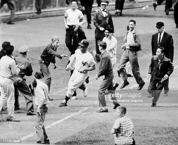 View of spectators on the field as they congratulate American baseball player Mickey Mantle , of the New York Yankees, as he runs towards home plate...