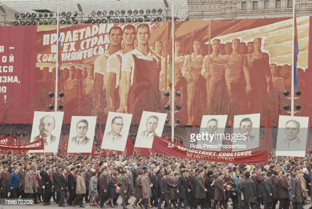 View of spectators some holding flags banners and images of Soviet leaders as they watch and applaud fellow citizens marching in the May Day Parade...