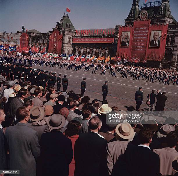 View of spectators watching participants carrying banners and flags march past the GUM store in Red Square Moscow during a Soviet era May Day parade...
