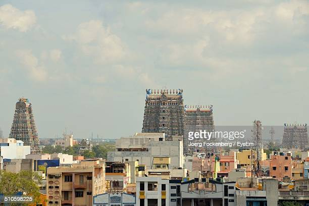 View of Sri Meenakshi Temple and residential buildings against cloudy sky