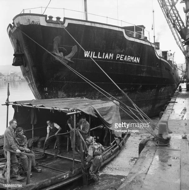 View of 'SS William Pearman' moored at the coaling wharf for Plymouth 'B' Power Station during its construction, showing workers aboard a smaller...