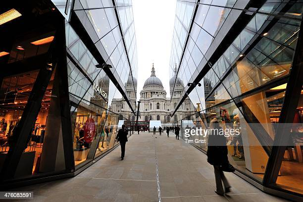 View of St Paul's Cathedral from One New Change with shop windows in view and shoppers walking along the pavement.
