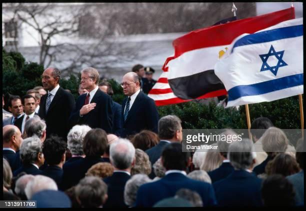 View of, standing center, from left. Egyptian President Anwar El-Sadat, US President Jimmy Carter, and Israeli Prime Minister Menachem Begin as they...