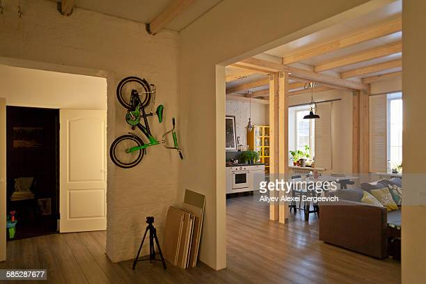 View of storage room, kitchen, dining area, couch and bicycle on wall
