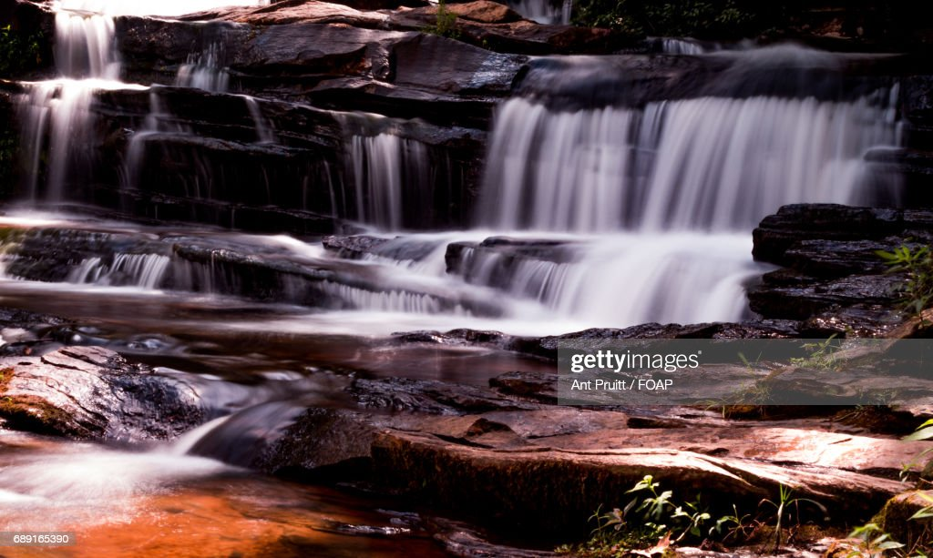 View of stream flowing through rock : Stock Photo