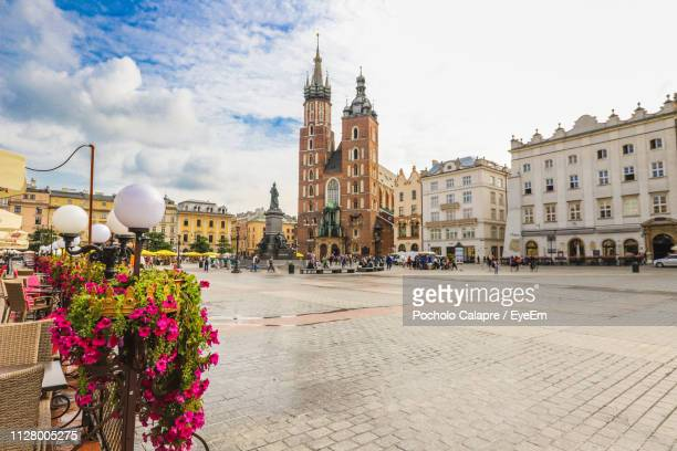 view of street and buildings against cloudy sky - krakow stock pictures, royalty-free photos & images