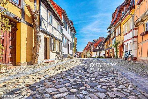 view of street and half-timbered houses - quedlinburg stock-fotos und bilder