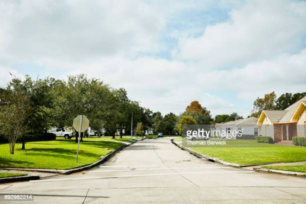 view of street in residential neighborhood on sunny afternoon - suburban stock pictures, royalty-free photos & images