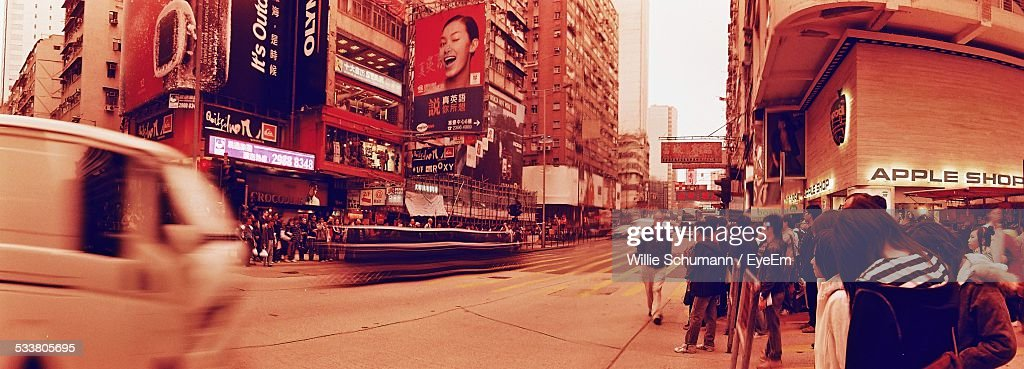 View Of Street With Shops, Commercial Signs And Crowd : Stock Photo