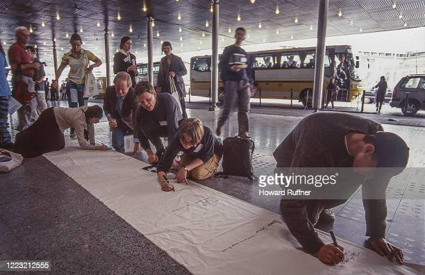View of students and others as they write messages on a banner at the Netherlands Convention Center during the Hague Appeal for Peace conference, the...