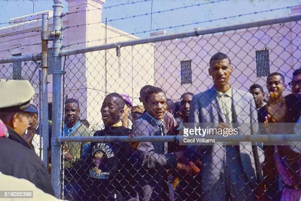 View of students as they stand behind a chainlink fence outside the Orangeburg County Jail following their arrest during an antisegregation...