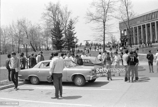 View of students gathered around a parked car with broken windows caused by bullets after the Ohio National Guard opened fire on antiwar protesters...