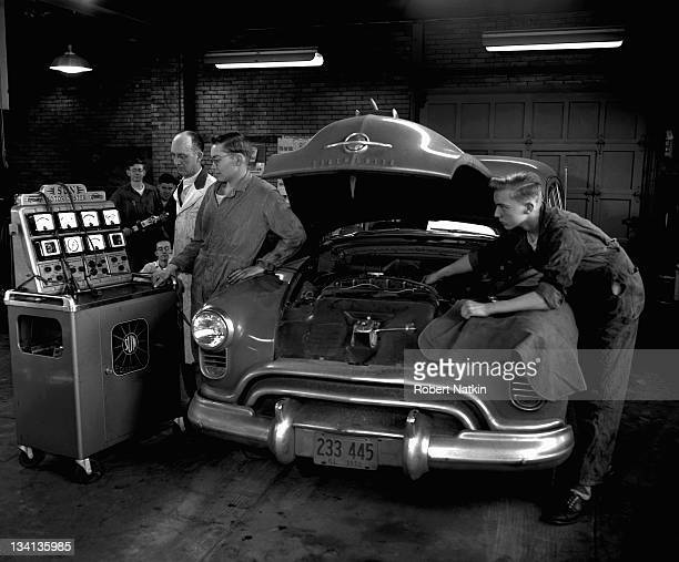 View of students honing their mechanical skills during an auto shop class at Morton High School Chicago 1952