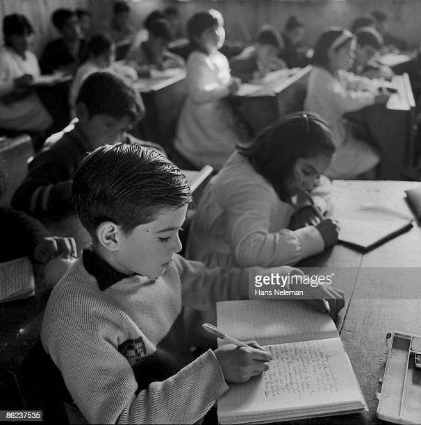 View of students in a classroom as they write in composition books at their desk, Peumo, O'Higgins Region, Chile, May 18, 1950.