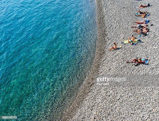 HIGH ANGLE view of SUNBATHERS ON BEACH