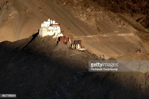 View of sunlight shining on Namgyal Tsemo Monastery with sand mountain background, Ladakh, India