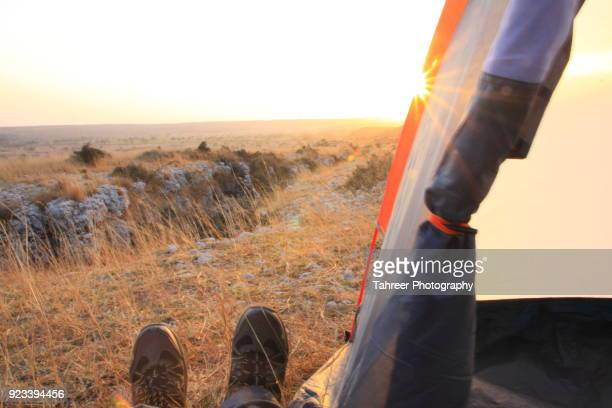 View of sunset and hiking shoes from a camp