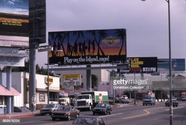 View of Sunset Blvd looking East from Marmont in January 1987 with a billboard for the Tropicana and a liquor stor and the Coconut Teaser and...