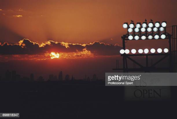 View of sunset over the skyline of Manhattan and New York with floodlights illuminating play inside the Louis Armstrong Stadium during the 1990 US...