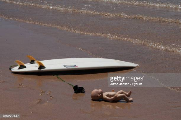 View Of Surfboard And Doll On Beach