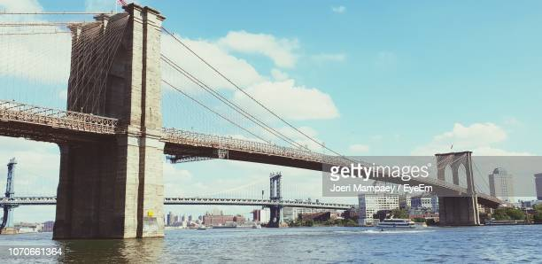view of suspension bridge against cloudy sky - south street seaport stock pictures, royalty-free photos & images