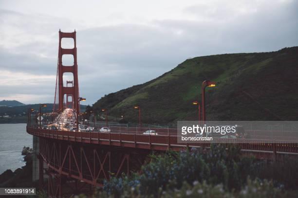 view of suspension bridge against cloudy sky - bortes stockfoto's en -beelden