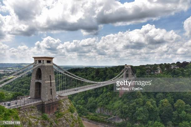 view of suspension bridge against cloudy sky - suspension bridge stock photos and pictures
