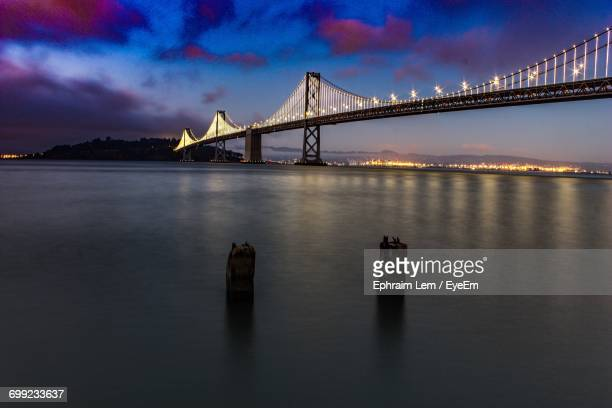 view of suspension bridge in city at night - ephraim lem stock pictures, royalty-free photos & images