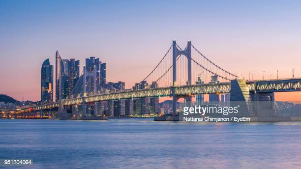 view of suspension bridge in city at night - south korea stock pictures, royalty-free photos & images