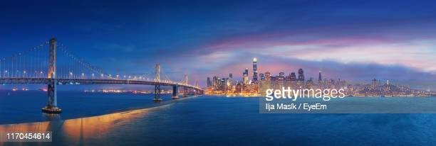 view of suspension bridge over sea against cloudy sky - oakland california skyline stock pictures, royalty-free photos & images