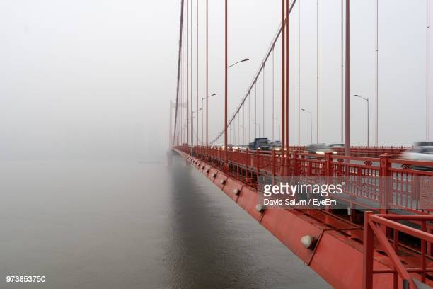 view of suspension bridge over sea against sky - wuhan stock photos and pictures