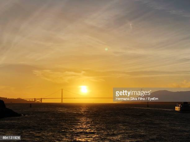 view of suspension bridge over sea during sunset - filho stock pictures, royalty-free photos & images