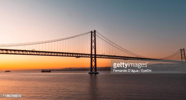 view of suspension bridge over sea - água stock pictures, royalty-free photos & images