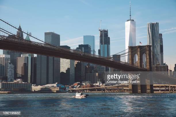 view of suspension bridge with city in background - bortes stock pictures, royalty-free photos & images