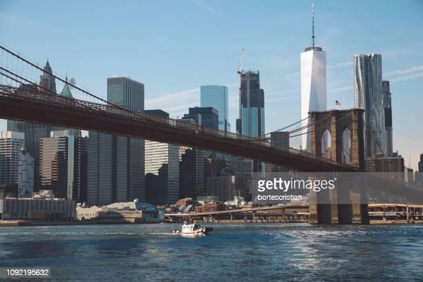 view of suspension bridge with city in background - bortes foto e immagini stock
