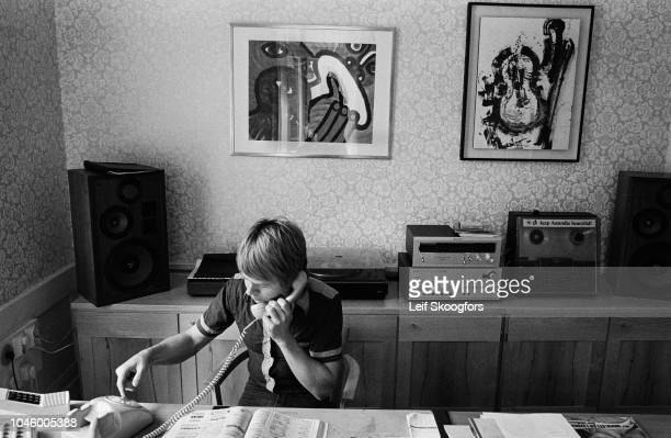 View of Swedish Pop musician Bjorn Ulvaeus talks on the telephone at a desk in his home Stockholm Sweden July 1977