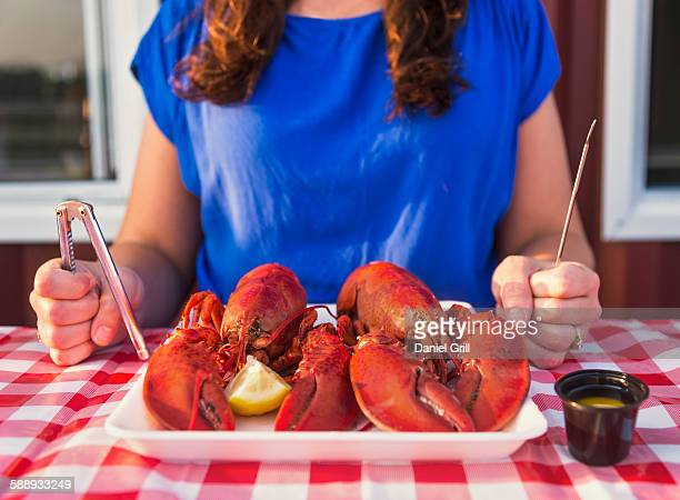View of table with lobster meal and woman preparing to eat