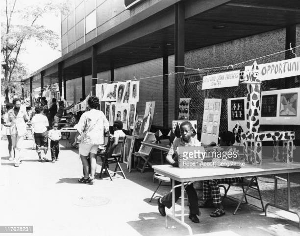 View of tables at an outdoor art gallery set up on the sidewalk possibly in the Englewood neighborhood of Chicago's southwest side late twentieth...
