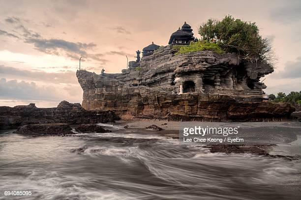 view of tanah lot rock formation against cloudy sky - denpasar stock pictures, royalty-free photos & images
