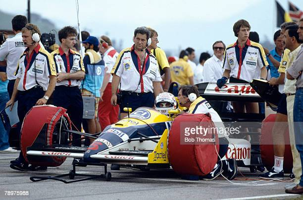 View of technical staff and mechanics working on the Canon Williams Williams FW12 Judd CV 35 V8 car of British racing driver Nigel Mansell in the...