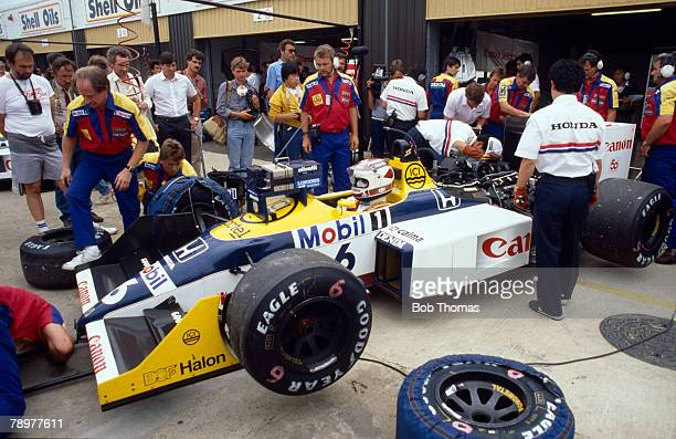 View of technical staff and mechanics working on the Canon Williams Team Williams FW11B Honda V6 t car of Brazilian racing driver Nelson Piquet in...