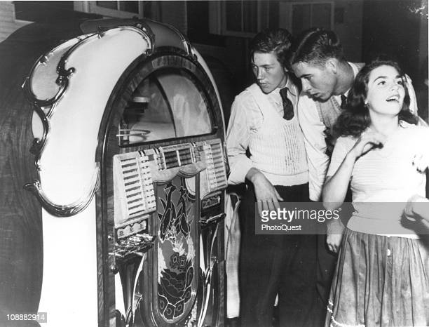 View of teenagers in Richwood West Virginia enjoying the music and perusing the list of songs from a Wurlistzer Model 850 jukebox 1942