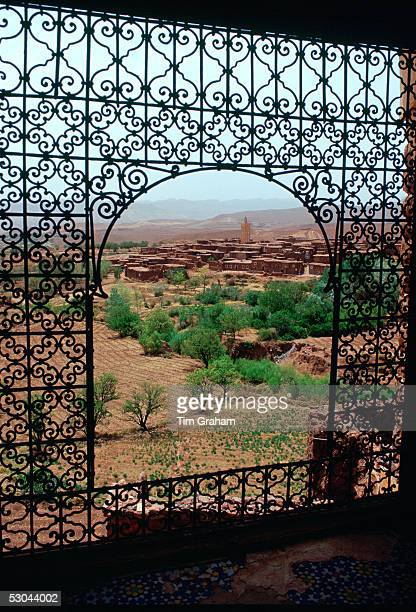 View of Telouet through an arched window decorated with ornamental filigree wrought iron work from Telouet Kasbah, Morocco.
