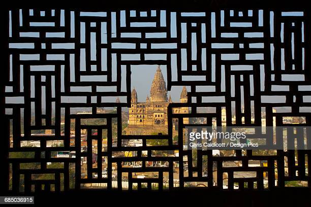 View of temple through carved stone screen window of Rajput palace