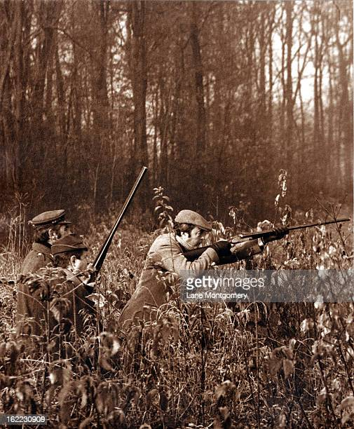 View of the 11th Duke of Marlborough John Spencer Churchill crouching down and taking aim while accompanied by two unidentified men on a pheasant...