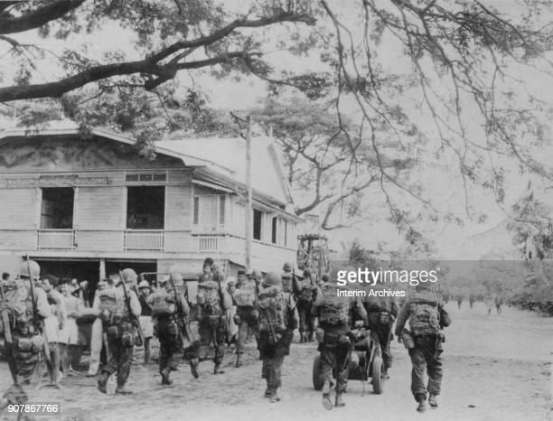 View of the 188th Glider Infantry Regiment as they walk past villagers gathered outside the Nasugbu Municipal Building, Nasugbu, Luzon, Philippines,...