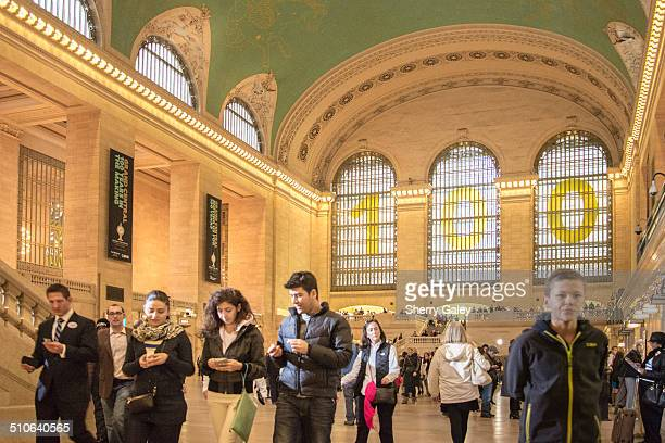 View of the 75foot Beaux Art windows of Grand Central Terminal decorated with the numbers 100 for the 2013 centennial Foreground has four people...