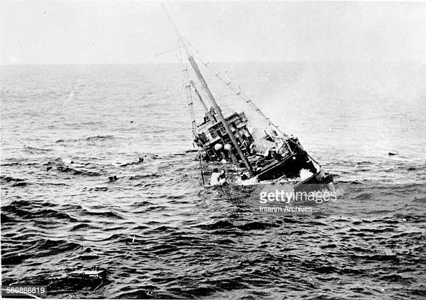 View of the aftermath of the sinking of a Japanese merchant ship by the US Navy submarine USS Tambor with survivors visible on the ship's rigging 1944
