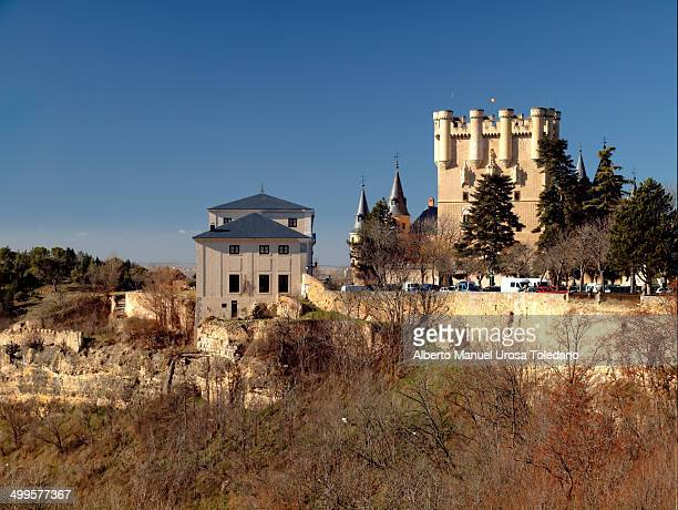 View of the Alcázar, the forest and the walls of Segovia around it. The Alcázar of Segovia is a stone fortification, located in the old city of...