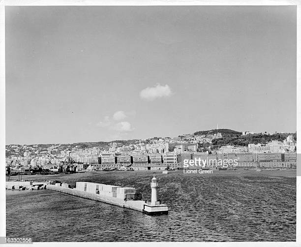 A view of the Algiers Harbor with buildings on the waterfront and mountains in the distance in Algieria North Africa 1955
